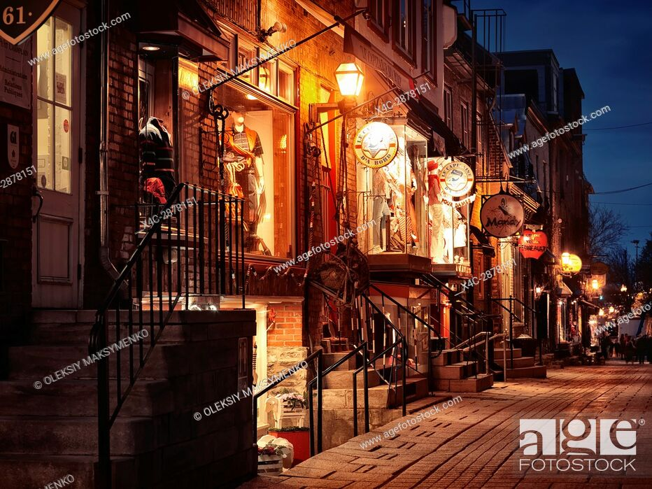 Stock Photo: Nighttime view of le Capitaine d'a bord, Mandy and other shops and restaurants on a historic street Rue du Petit Champlain in old Quebec City, Quebec, Canada.