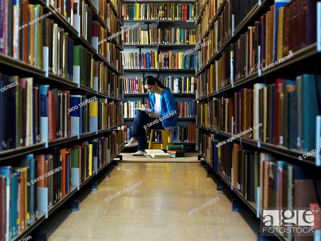 Stock Photo: Young woman reading by bookshelf in library.