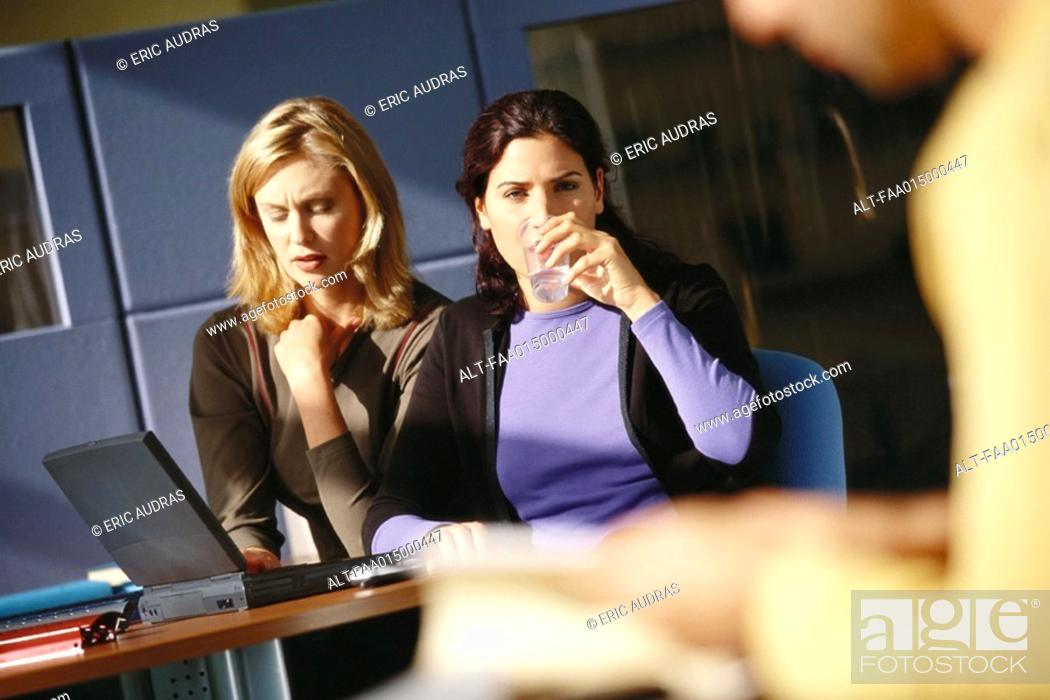 Stock Photo: Two female office workers using laptop, one drinking glass of water.