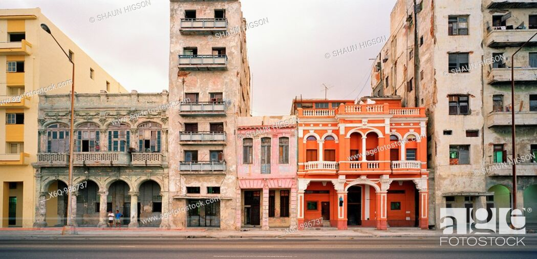 Stock Photo: A renovated building amongst other dilapidated buildings on the Malecon in Havana in Cuba in Central Latin America.
