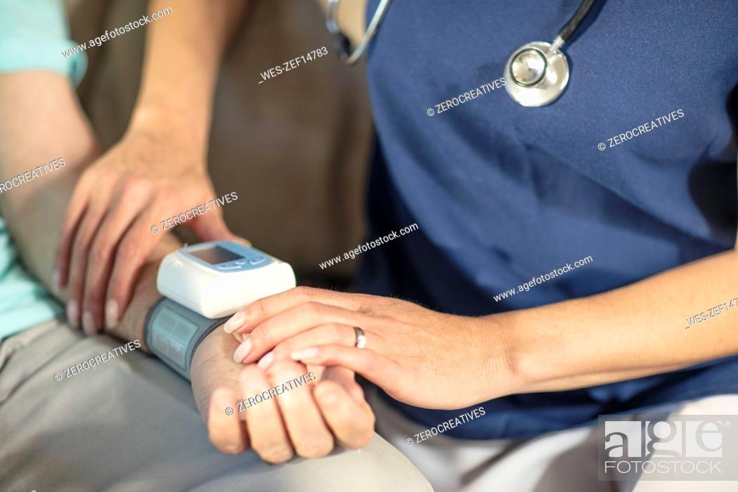 Stock Photo: Nurse taking blood pressure of senior patient at home.