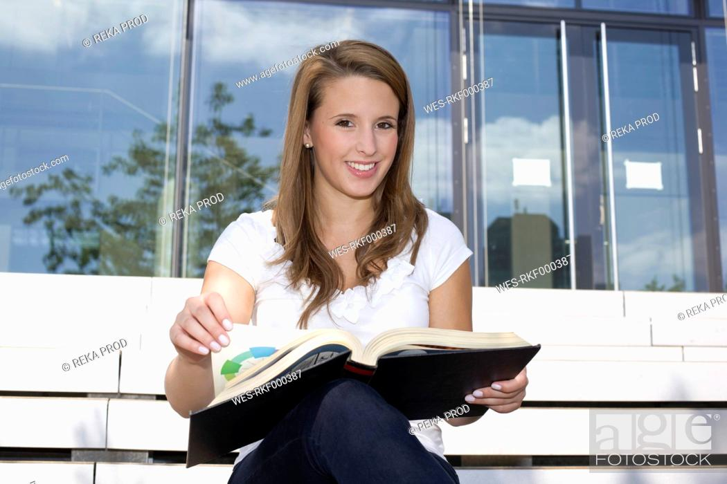 Stock Photo: Europe, Germany, North Rhine Westphalia, Duesseldorf, Young student sitting on staircase with book, smiling, portrait.