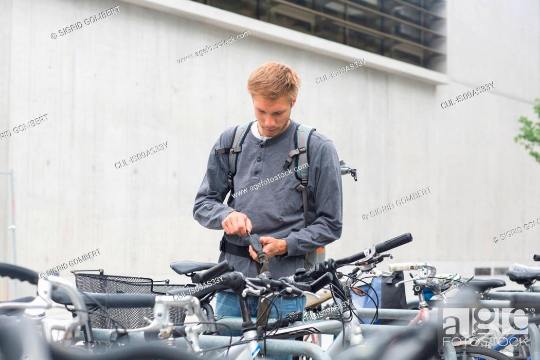 Photo de stock: Mid adult using key to lock, unlock bicycle lock, looking down.