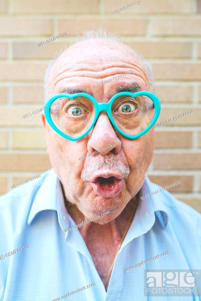 Stock Photo: Portrait of senior man wearing heart-shaped glasses pulling funny faces.
