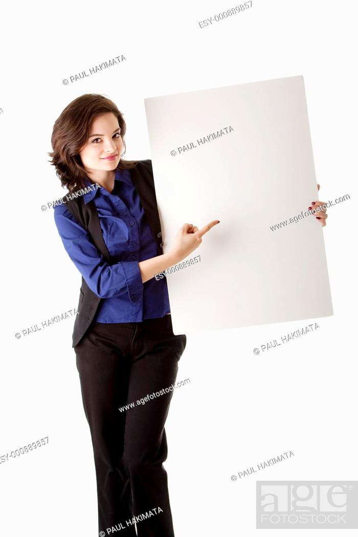 Stock Photo: Happy smiling beautiful young caucasian brunette business student woman standing next to and holding a white blank board and pointing at it, isolated.