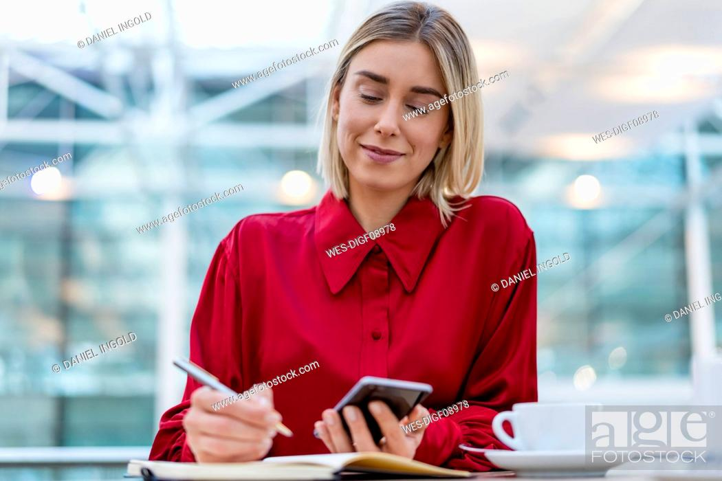 Stock Photo: Young businesswoman with cell phone taking notes in a cafe.