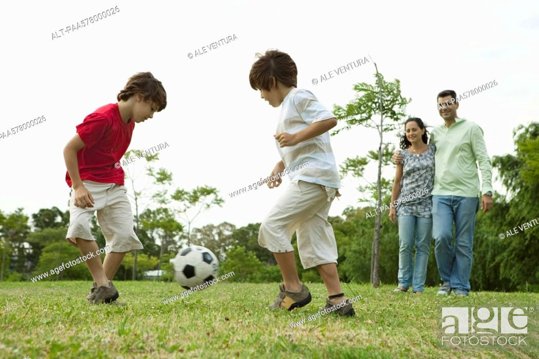 Stock Photo: Boys playing soccer, parents watching in background.
