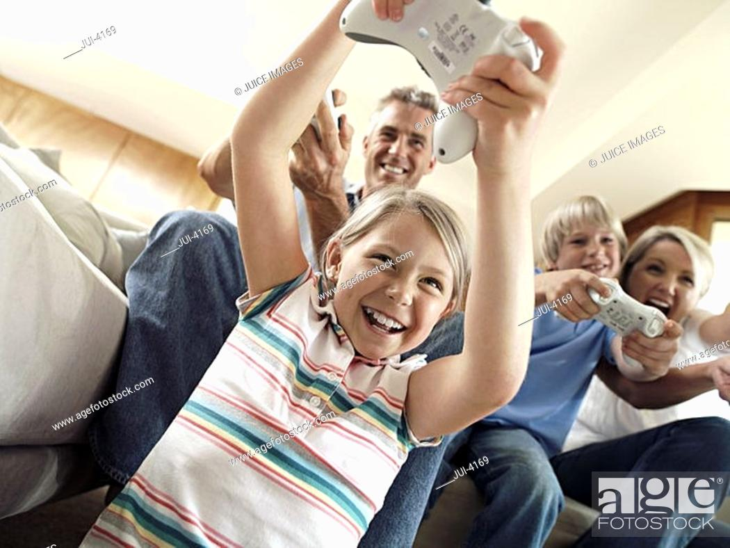 Stock Photo: Family sitting on sofa at home, playing with video games console, smiling, low angle view tilt.