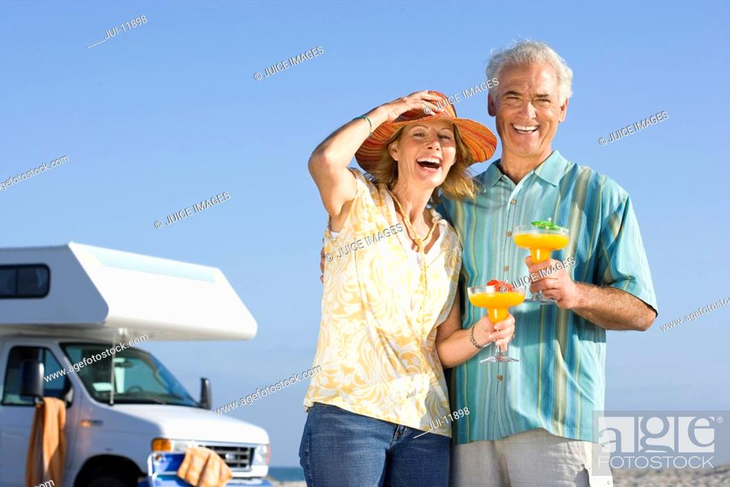 Stock Photo: Mature couple with cocktails by motor home on beach, smiling, portrait, low angle view.