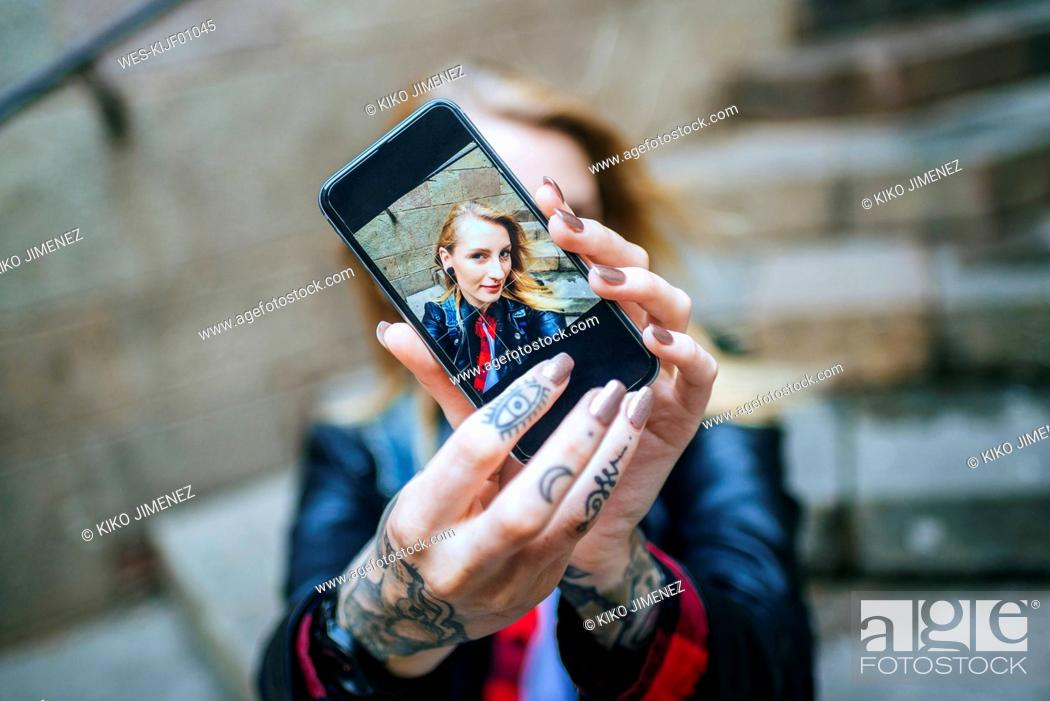 Stock Photo: Tattooed woman's hands taking selfie with smartphone, close-up.