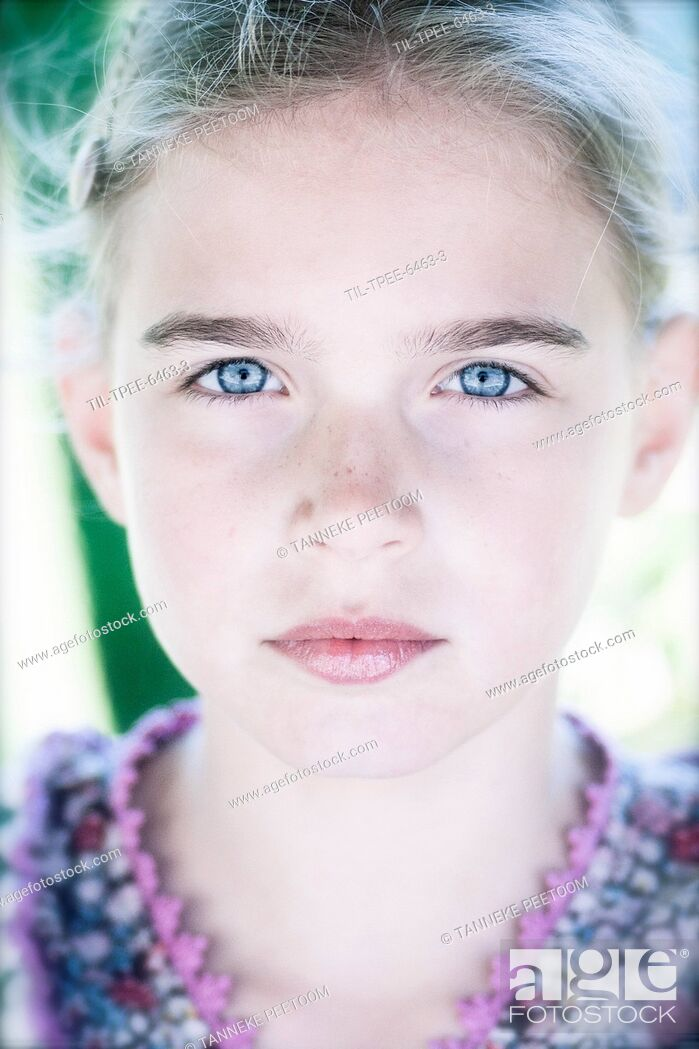 Stock Photo: Close up of a young girl with blonde hair and blue eyes looking directly into the camera.