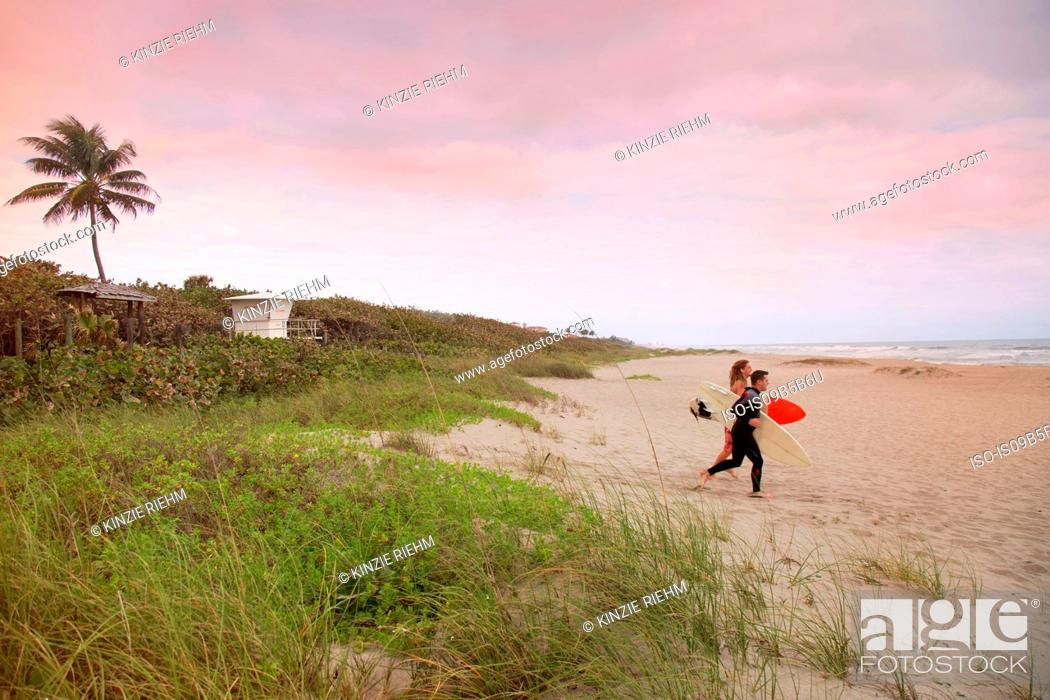Photo de stock: Male lifeguard and surfer running toward sea from beach.