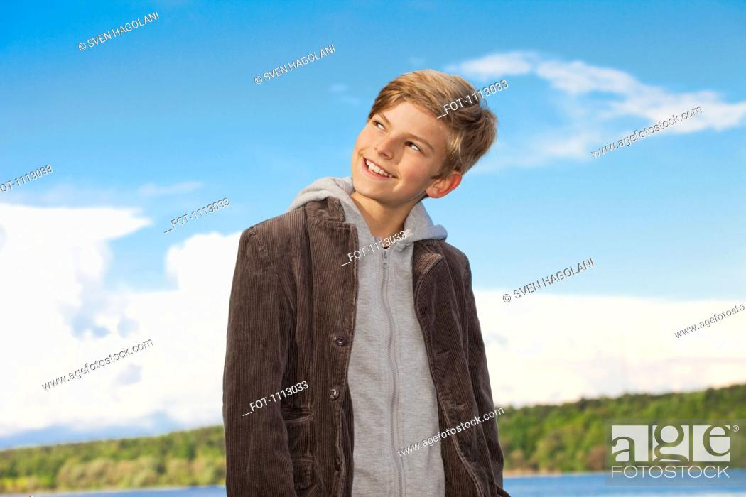 Stock Photo: Portrait of a boy looking away and smiling mischievously.