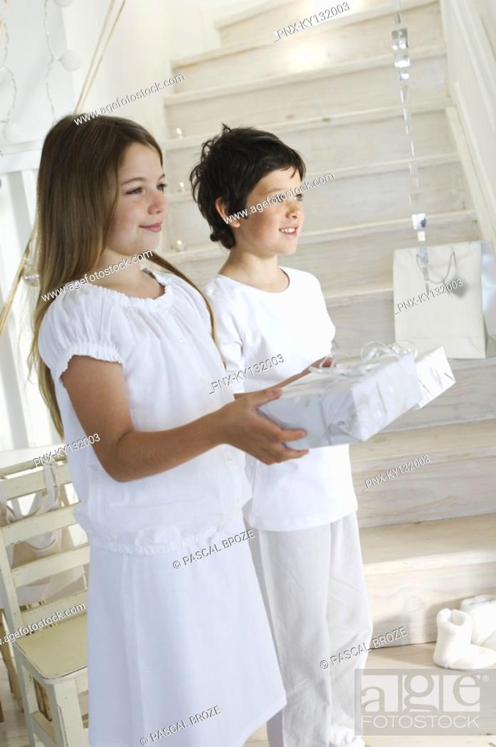 Stock Photo: Lillte girl and little boy offering Christmas presents, indoors.