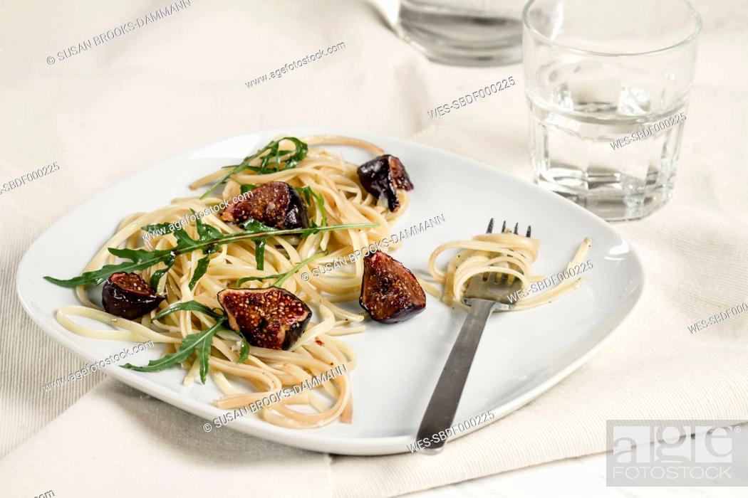 Stock Photo: Plate with fig tagliatelle, rocket leaves, sauce and a glass of water, studio shot.