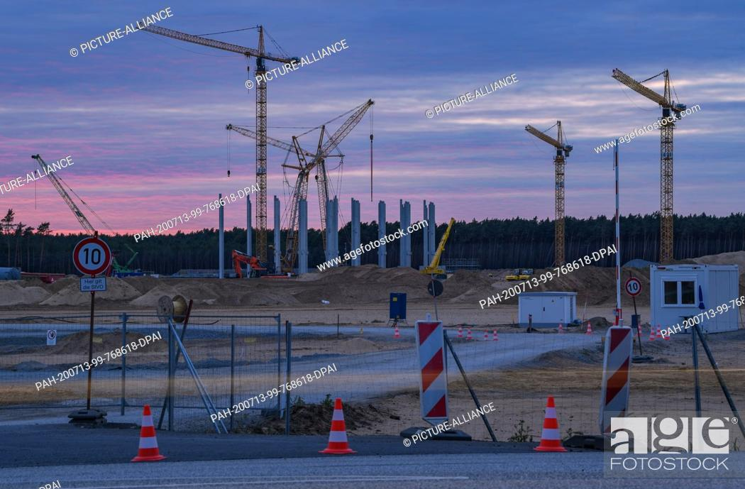 Stock Photo: 12 July 2020, Brandenburg, Grünheide: Late in the evening, cranes and first piers for the future Tesla Giga Factory can be seen on the construction site.