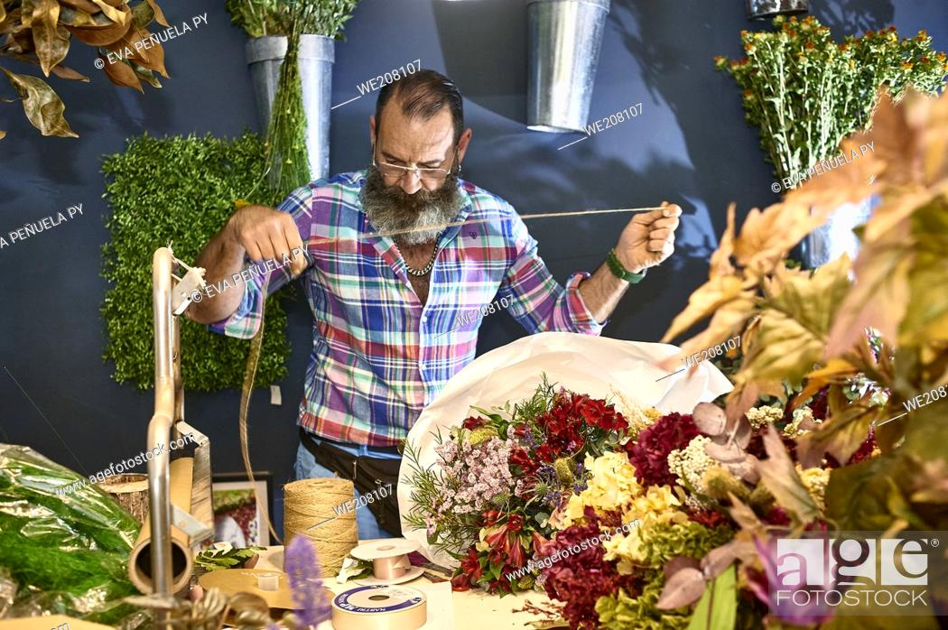 Imagen: A florist taking care of various flowers and bouquets in his shop.