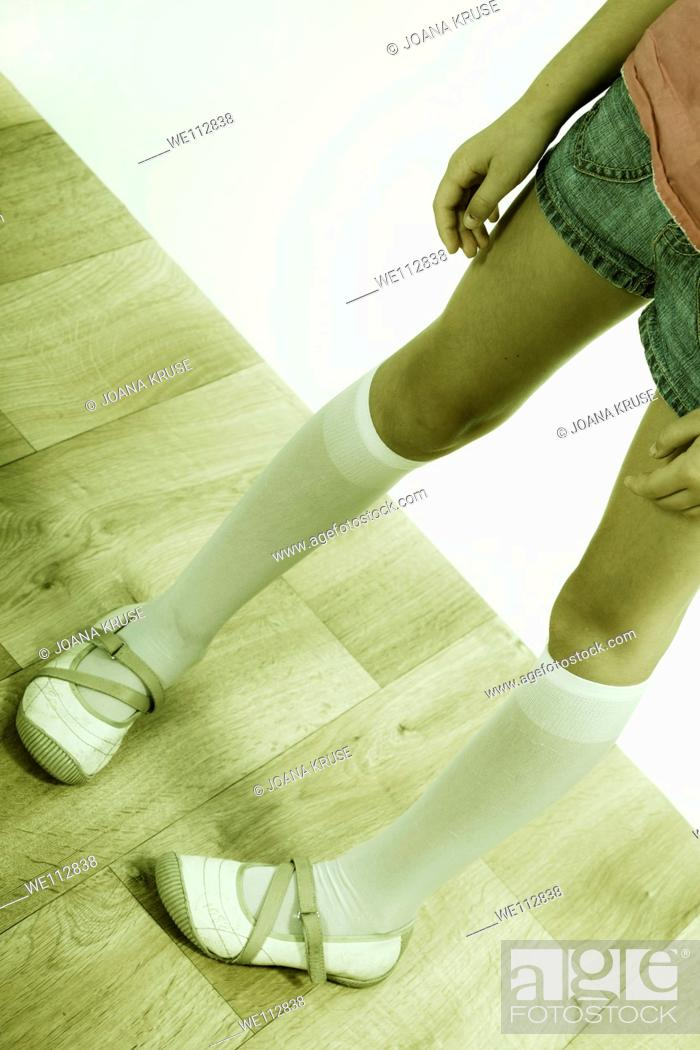 Stock Photo: the legs of a young girl in retro style.