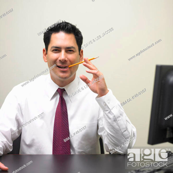 Stock Photo: Businessman chewing on pencil at desk.