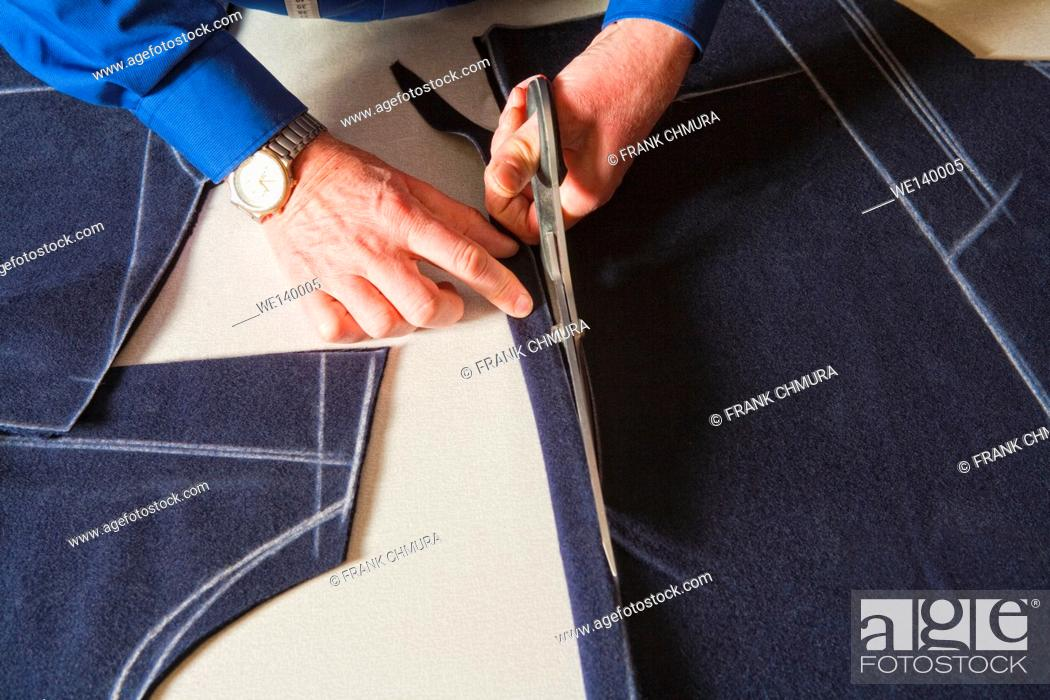 Stock Photo: Tailor Cutting Fabric to a New Coat with Scissors.