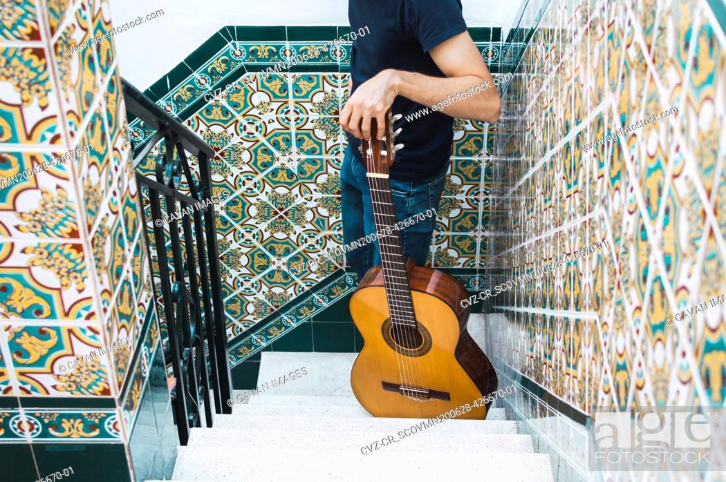 Imagen: Crop man standing on a staircase with a spanish guitar.