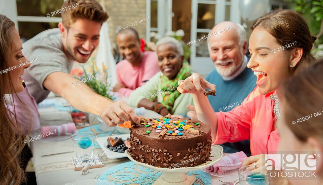 Imagen: Family reaching for candy on chocolate birthday cake at patio table.
