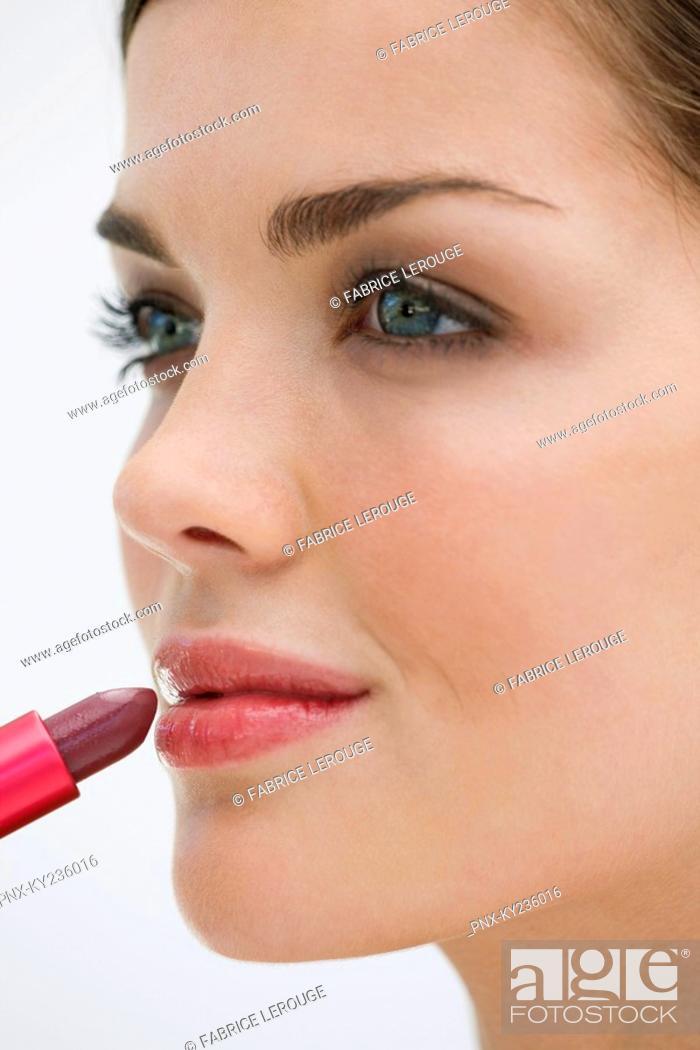 Stock Photo: Fashion model applying lipstick on her lips.