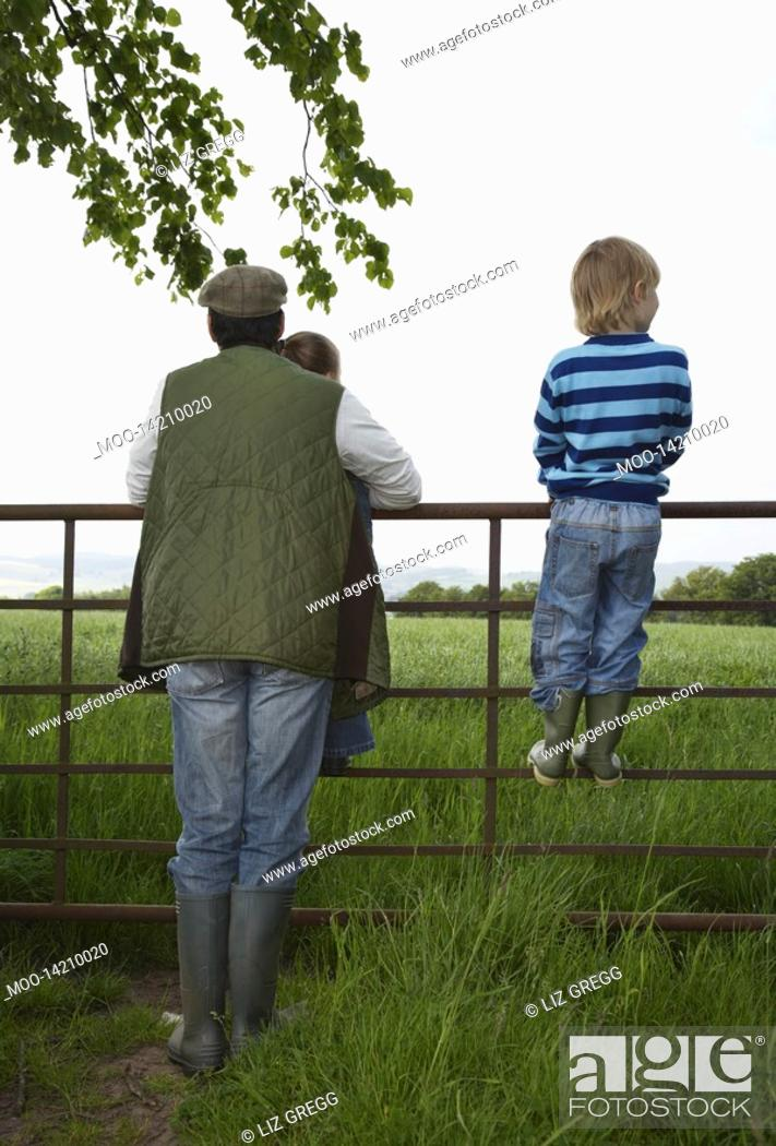 Stock Photo: Father with two children 5-6 standing by fence in countryside.