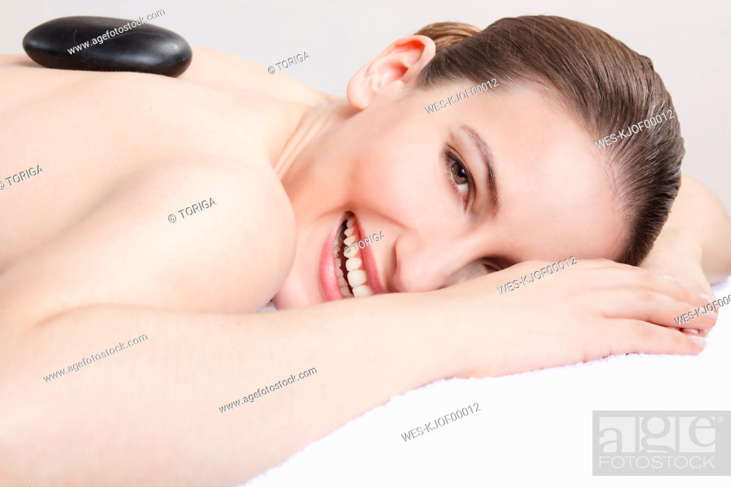 Stock Photo: Woman having a hot stone treatment, smiling, portrait.