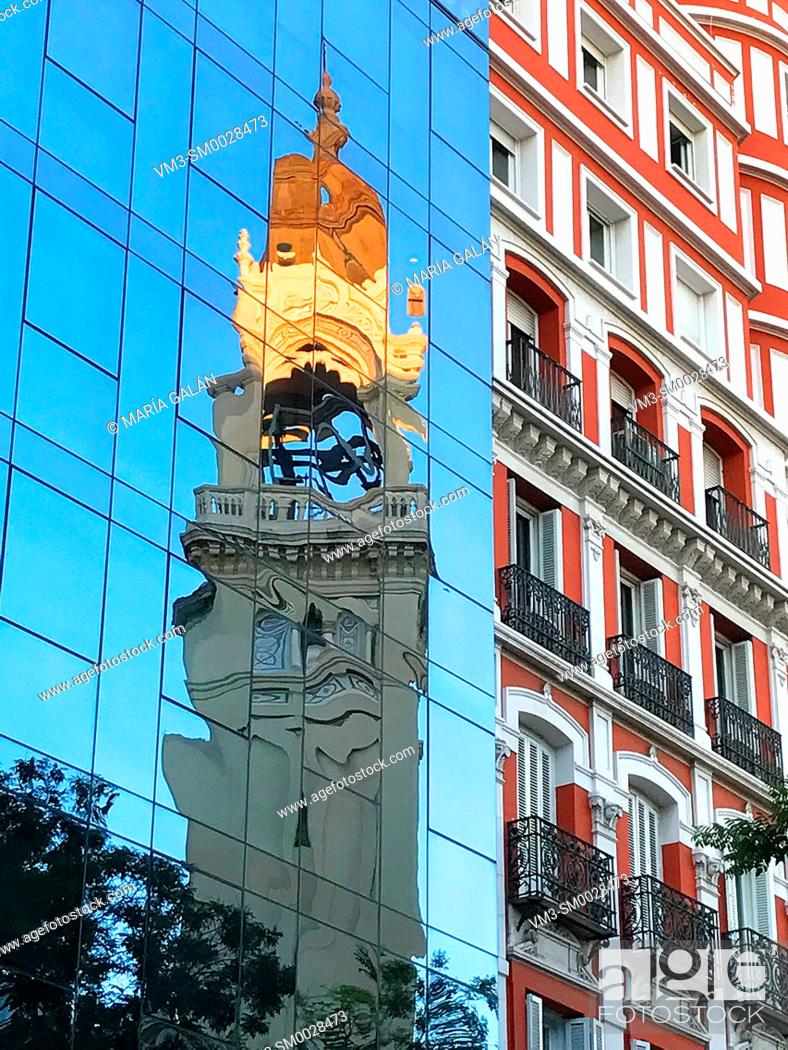 Stock Photo: Tower reflected on glass facade. San Manuel y San Benito church, Madrid, Spain.