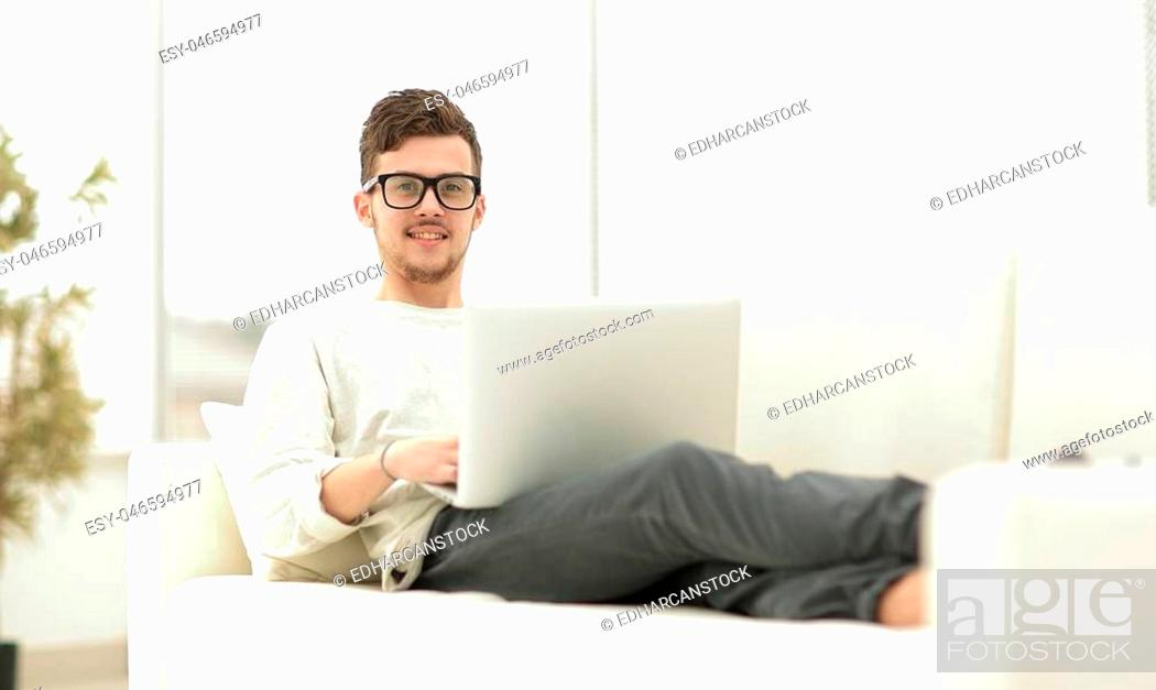 Stock Photo: successful young male freelancer working on laptop at home. photo with copy space.