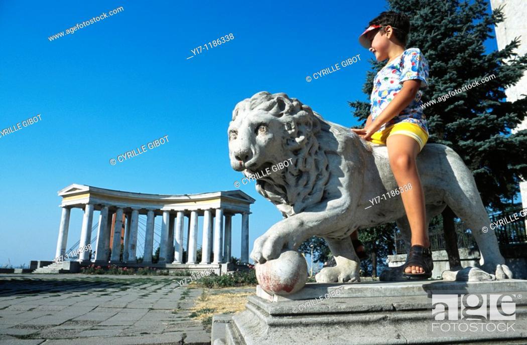 Stock Photo: Little boy sitting on lion statue, Odessa, Ukraine.