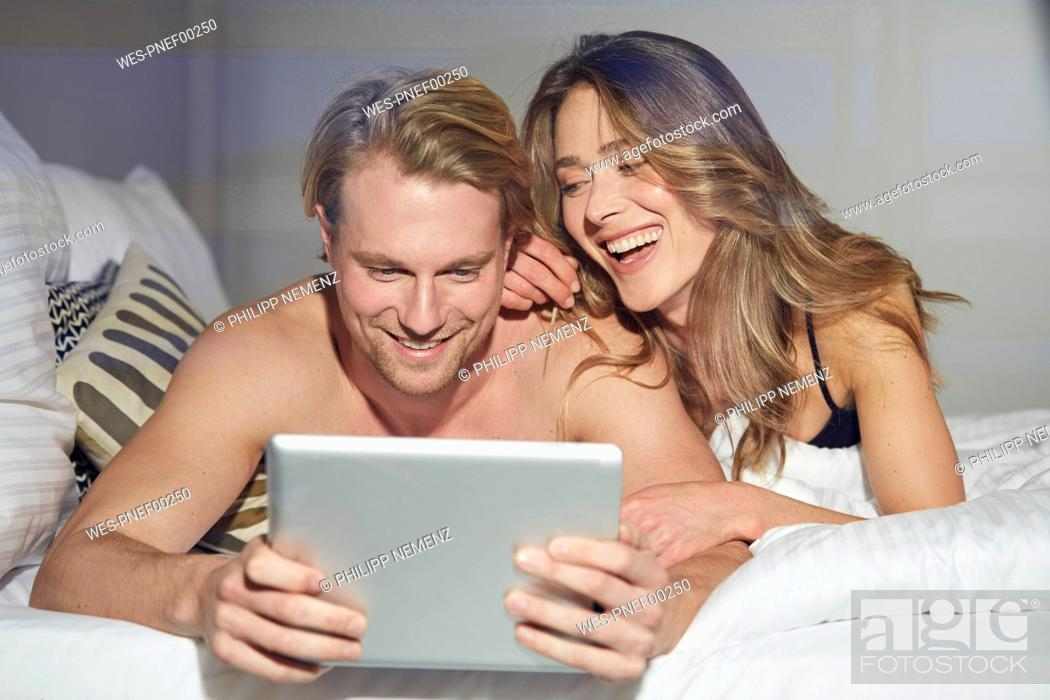 Stock Photo: Portrait of relaxed couple with tablet lying on bed.