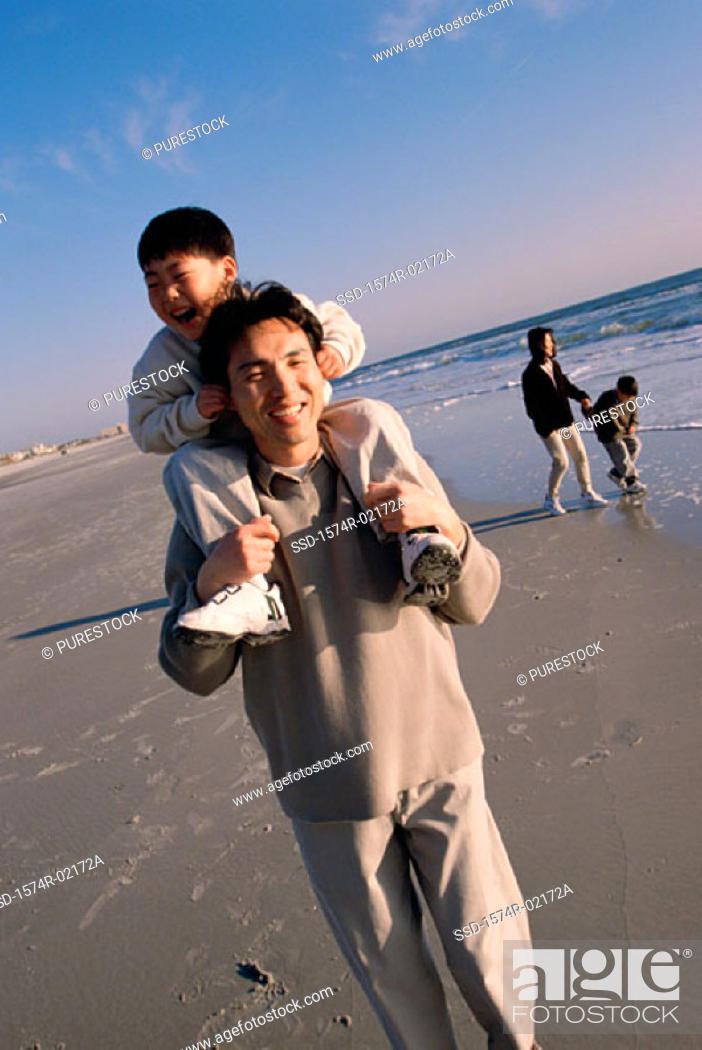 Stock Photo: Father carrying his son on his shoulders walking on the beach.