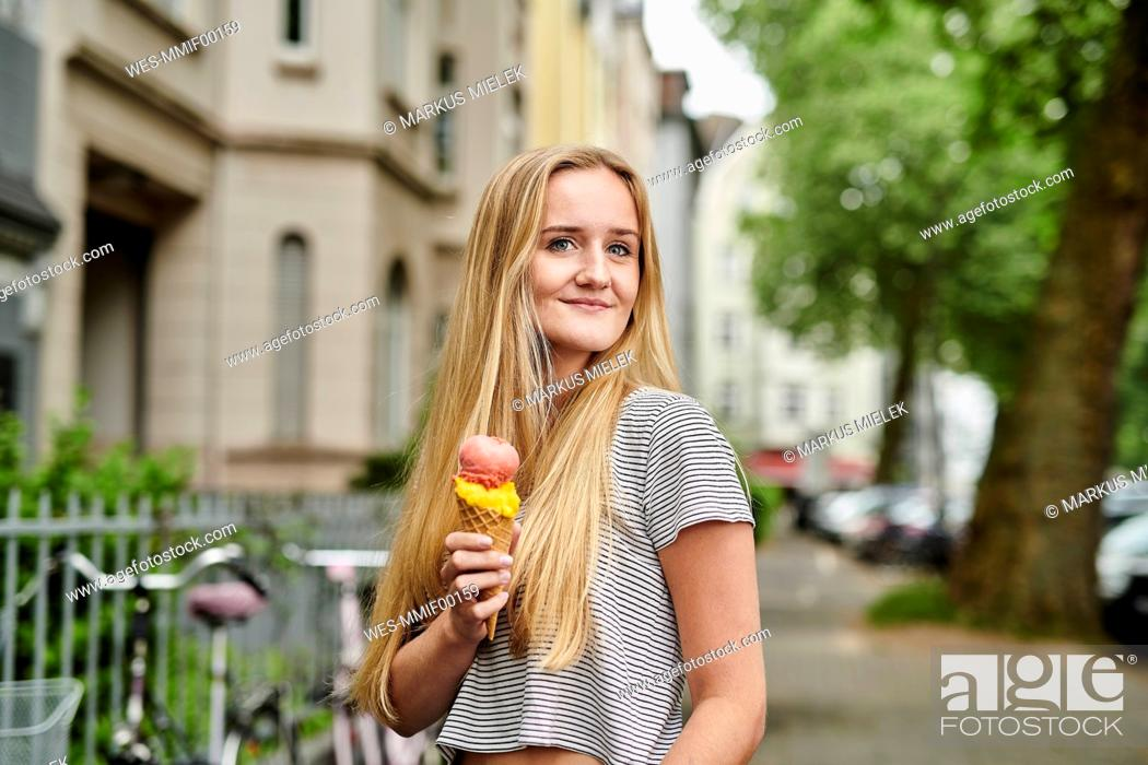 Stock Photo: Young woman enjoying an ice cream cone in the city.