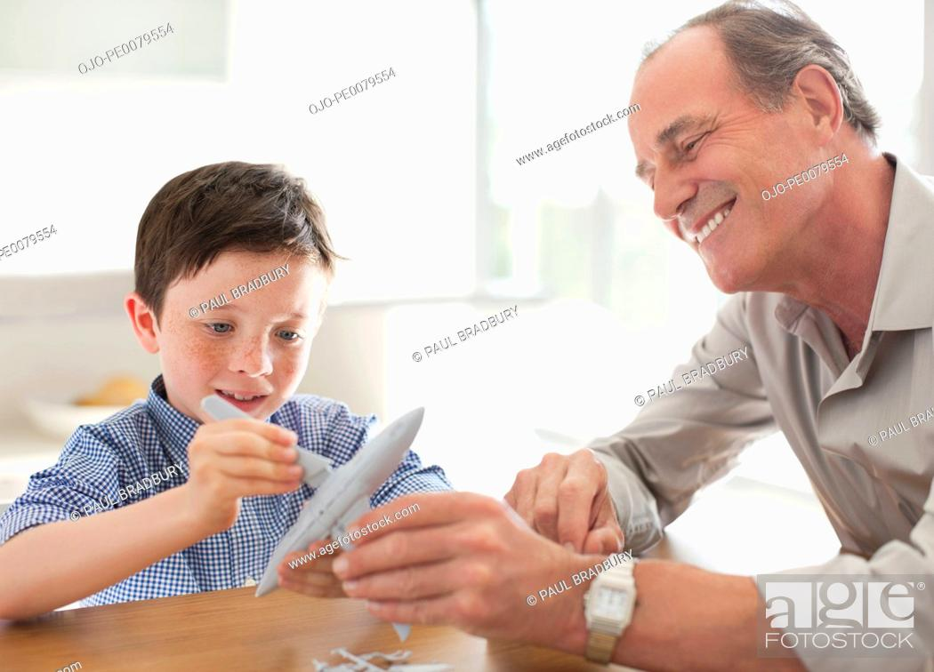 Stock Photo: Grandfather and grandson assembling airplane model.