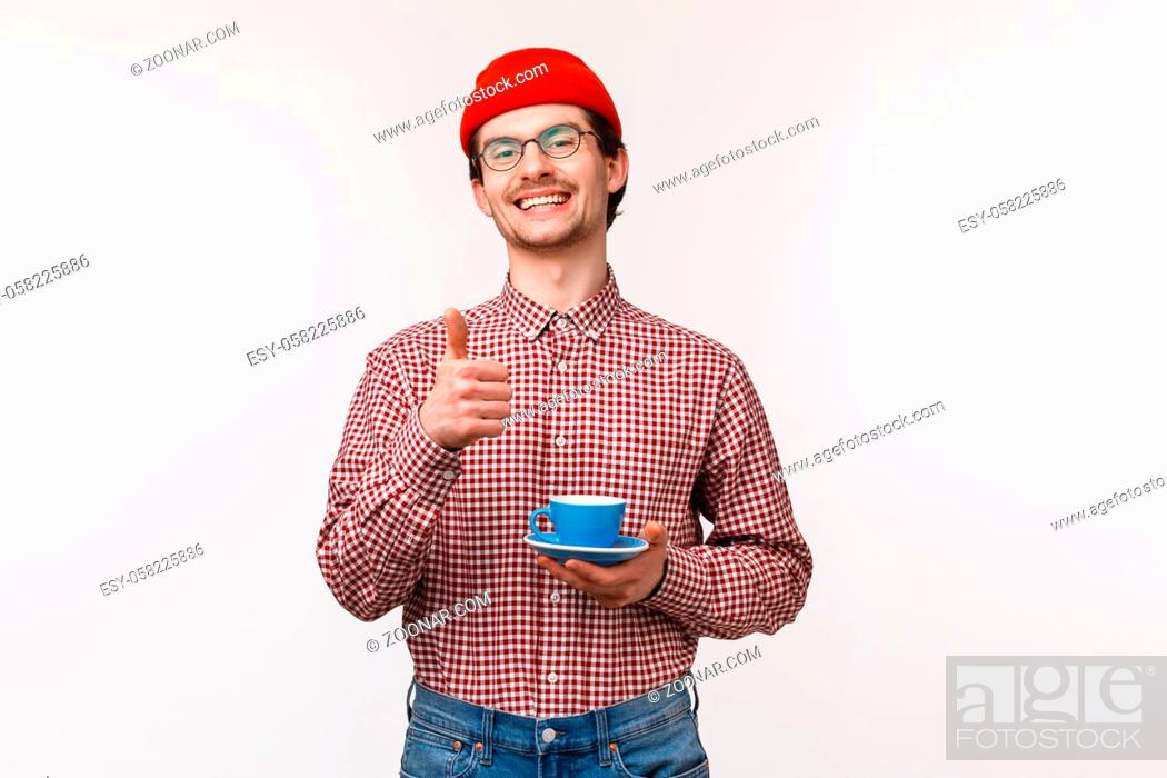Stock Photo: Pleased happy and relaxed smiling bearded man in glasses and red beanie, show thumb-up as holding cup with tea or coffee, satisfied with well made cappuccino.