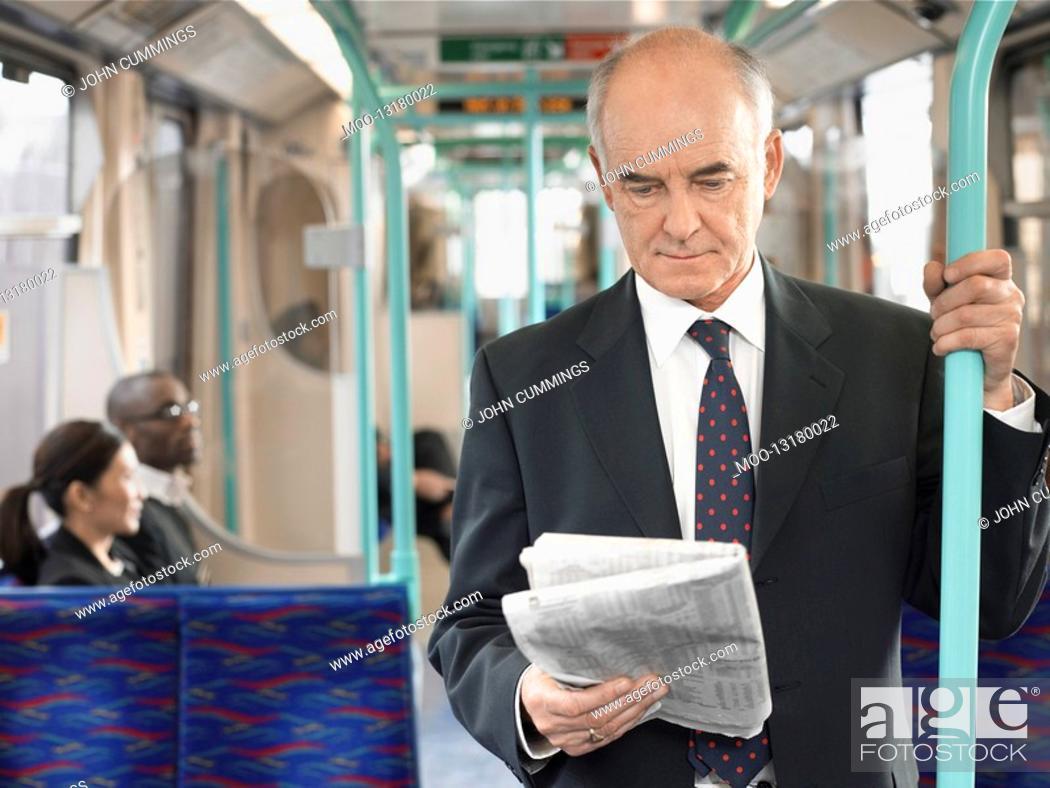Stock Photo: Businessman Reading Newspaper on Train holding onto bar.