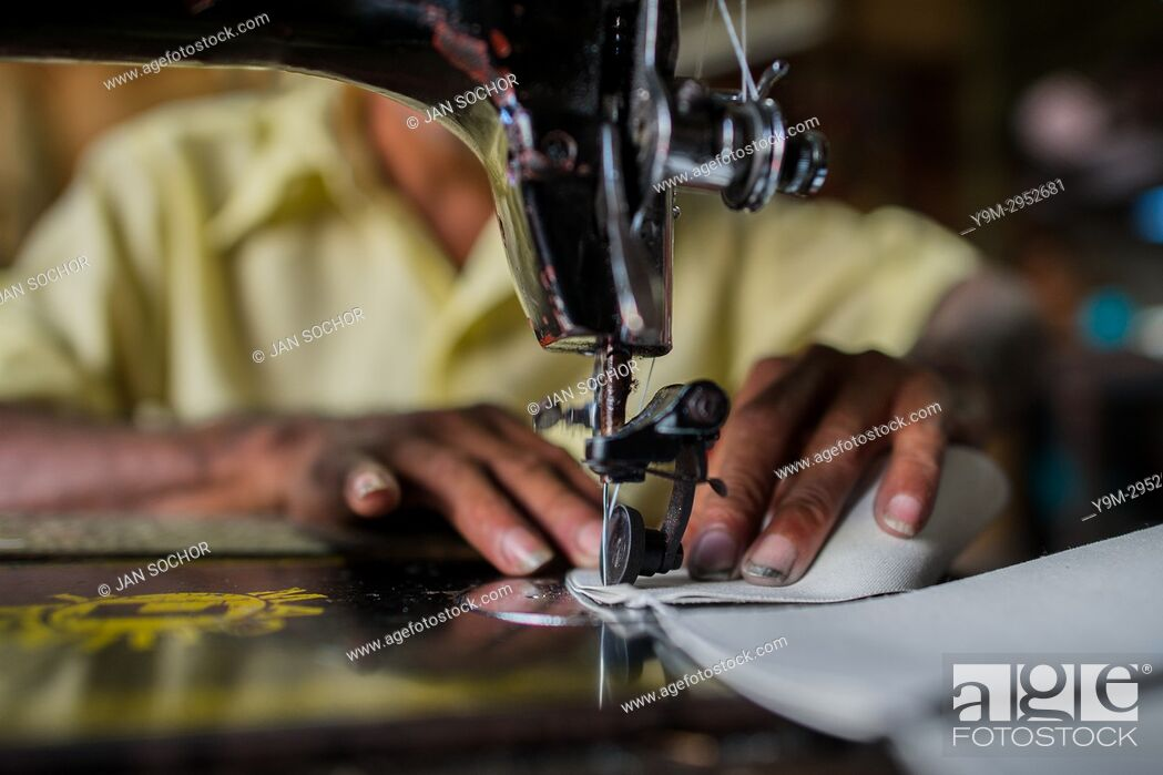 Stock Photo: A Salvadoran shoemaker works on a sewing machine, stitching shoe uppers, in a shoe making workshop in San Salvador, El Salvador.