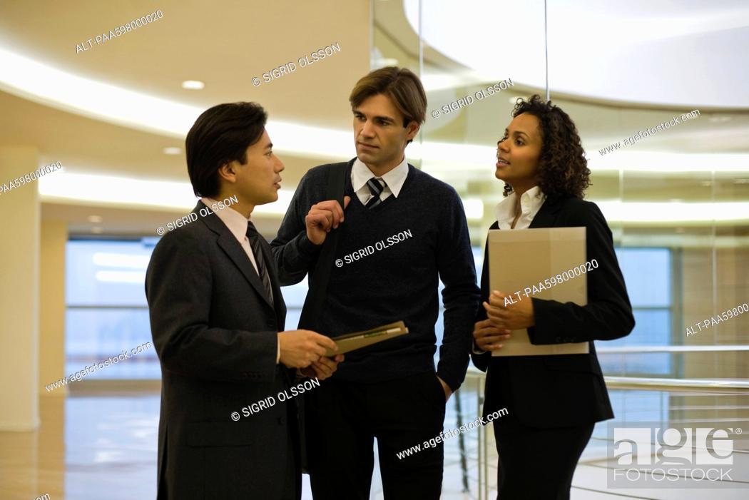 Stock Photo: Executives talking in corridor.