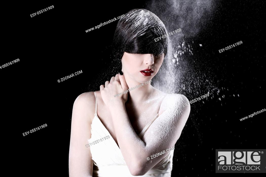 Stock Photo: Beautiful girl in white dress and flying dust over black background.