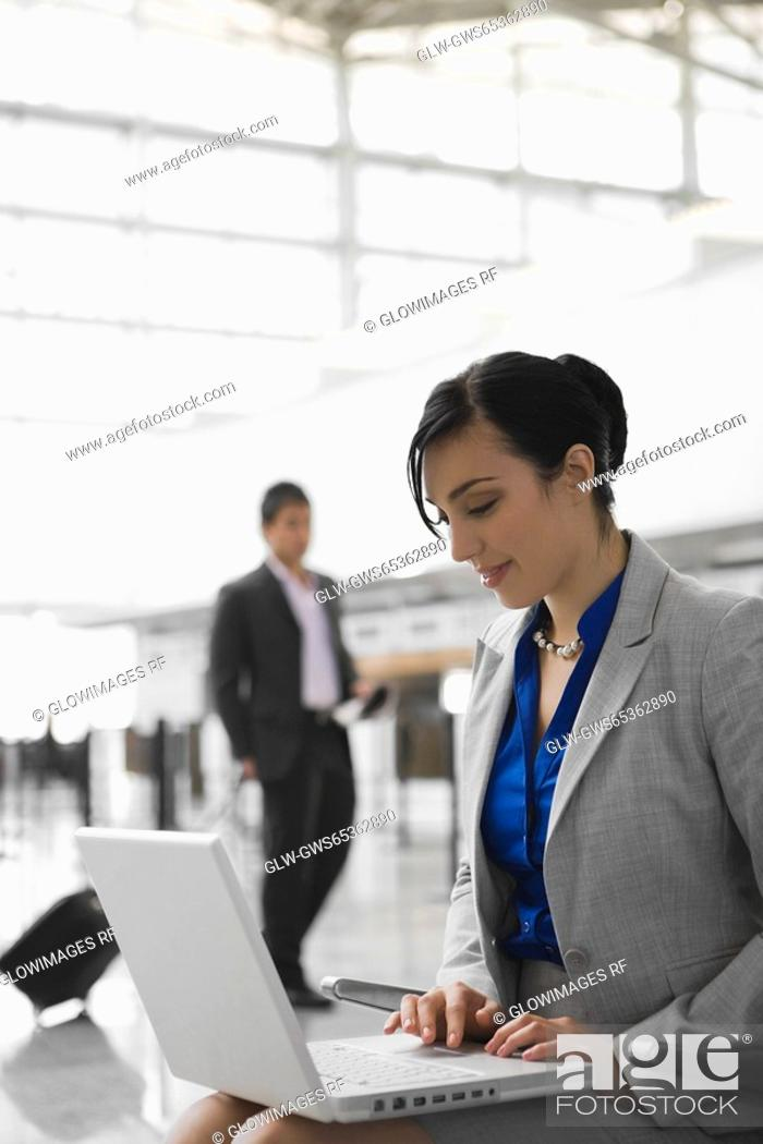 Stock Photo: Businesswoman sitting at an airport and using a laptop.