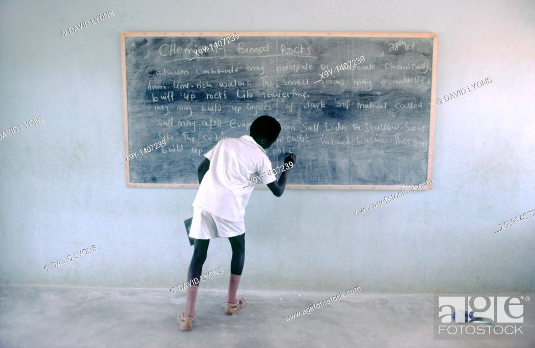 Stock Photo: Nigerian schoolboy writing on chalk blackboard in classroom during geology lesson  Nigeria.