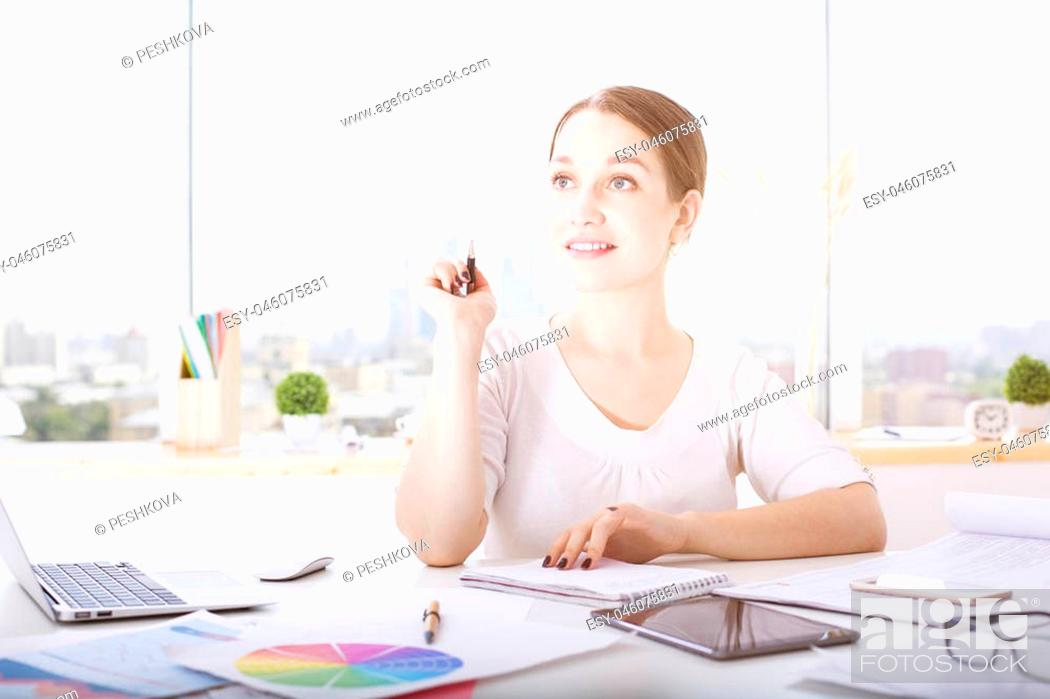 Stock Photo: Portrait of attractive thoughtful young lady sitting at office desk with electronic devices and paperwork.