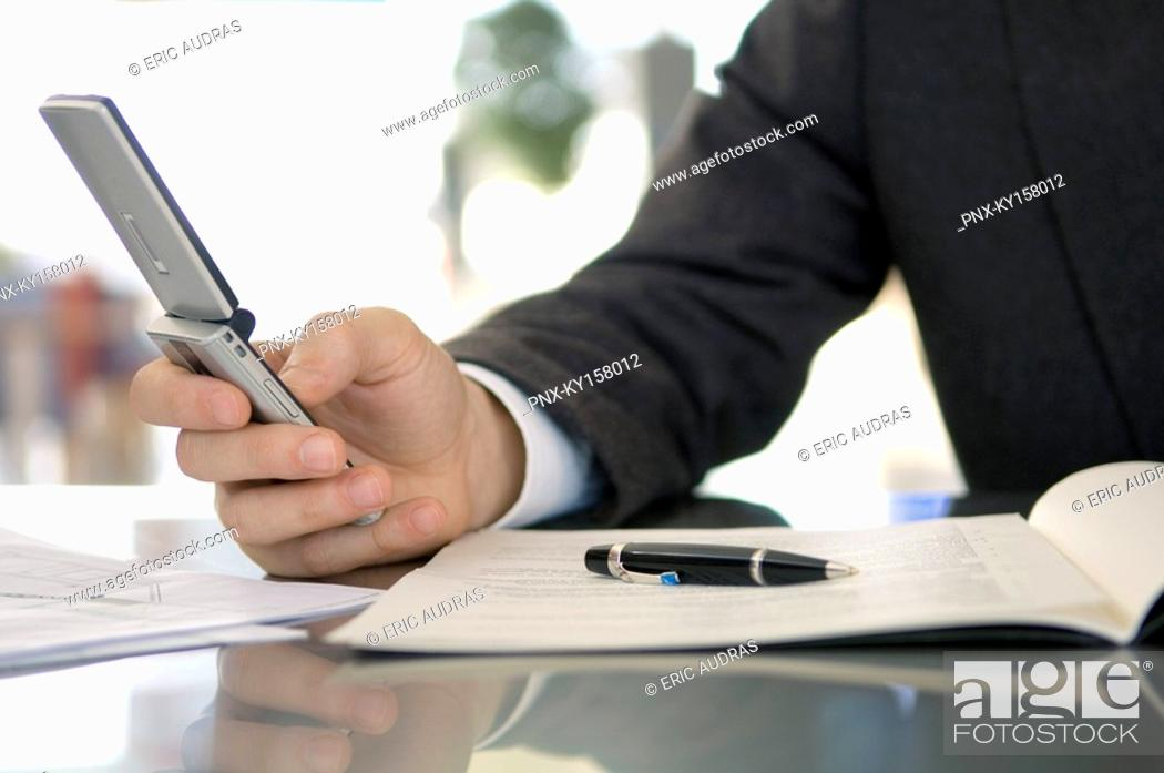 Stock Photo: Mid section view of a businessman using a mobile phone.