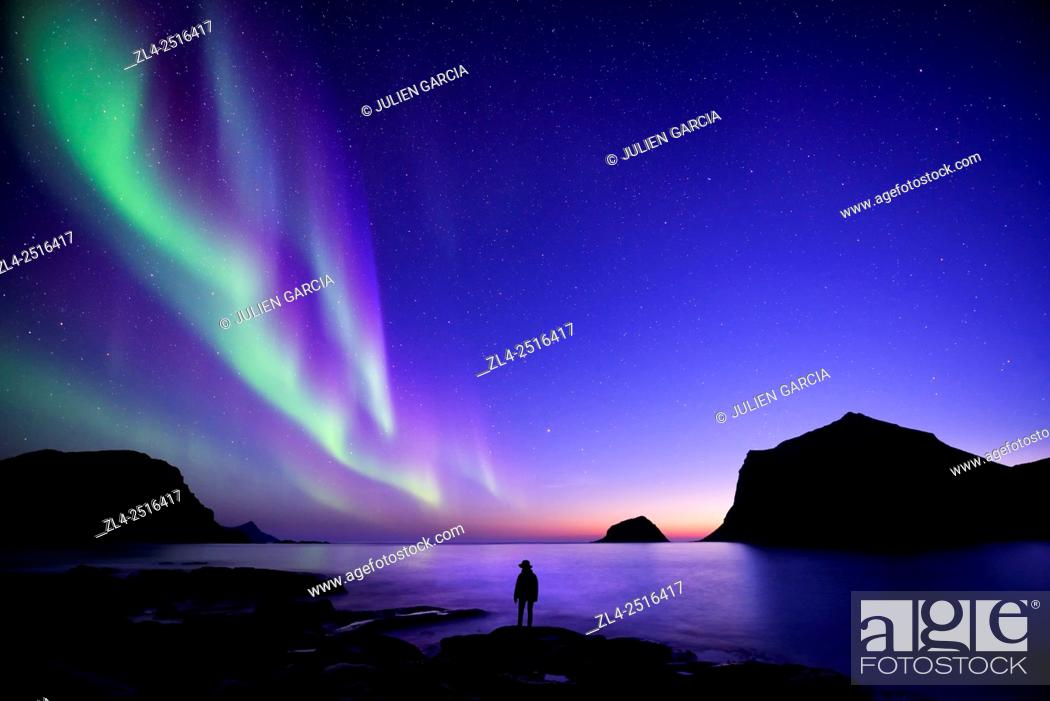 Stock Photo: Norway, Nordland, Lofoten islands, Vestvagoy island, Vik beach, silhouette of a woman and northern lights (aurora borealis), Model Released.