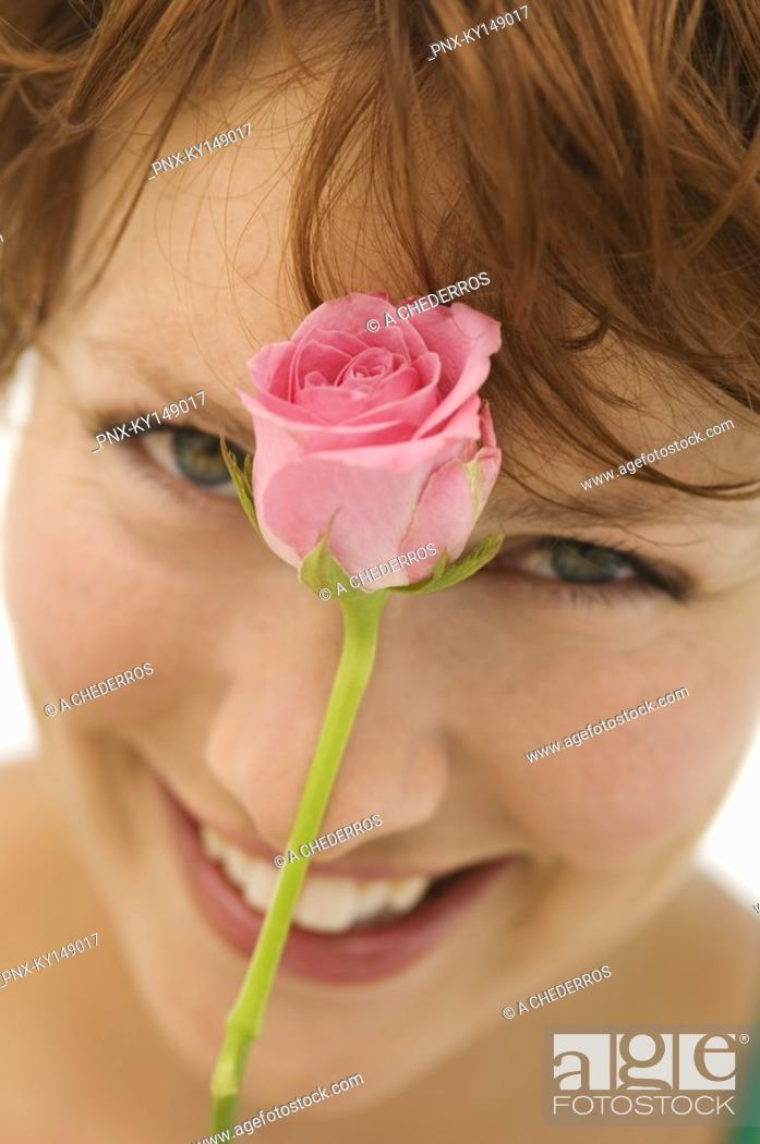 Stock Photo: Portrait of young woman with rose in front of face.