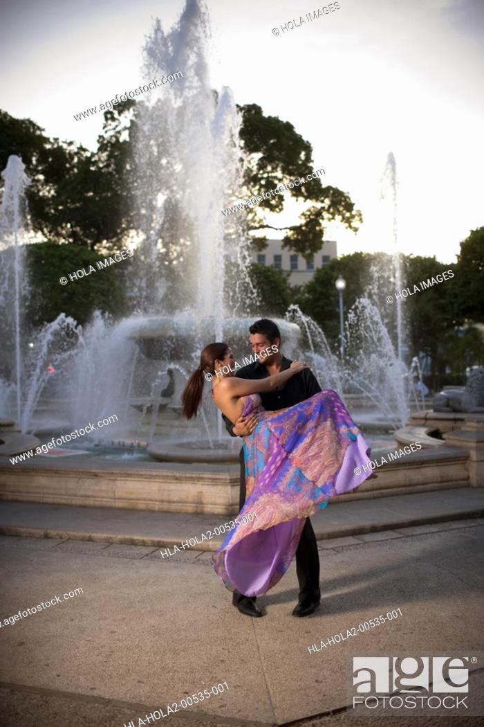 Imagen: Young man carrying woman by fountain.
