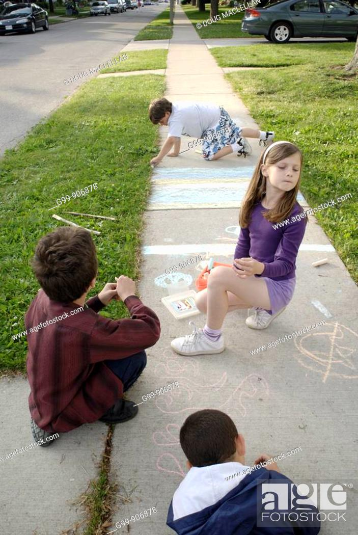 Stock Photo: Canada, Ontario, Windsor. Three boys and one girl drawing with chalk on a sidewalk during the summer.