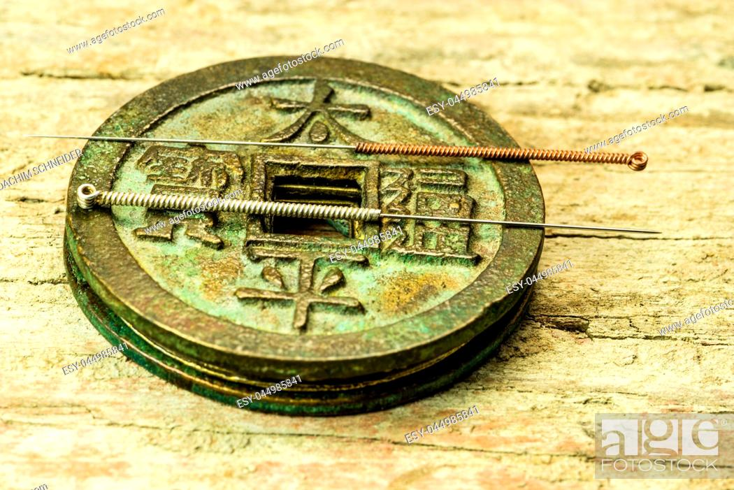 Stock Photo: acupuncture needles on antique Chinese coin.
